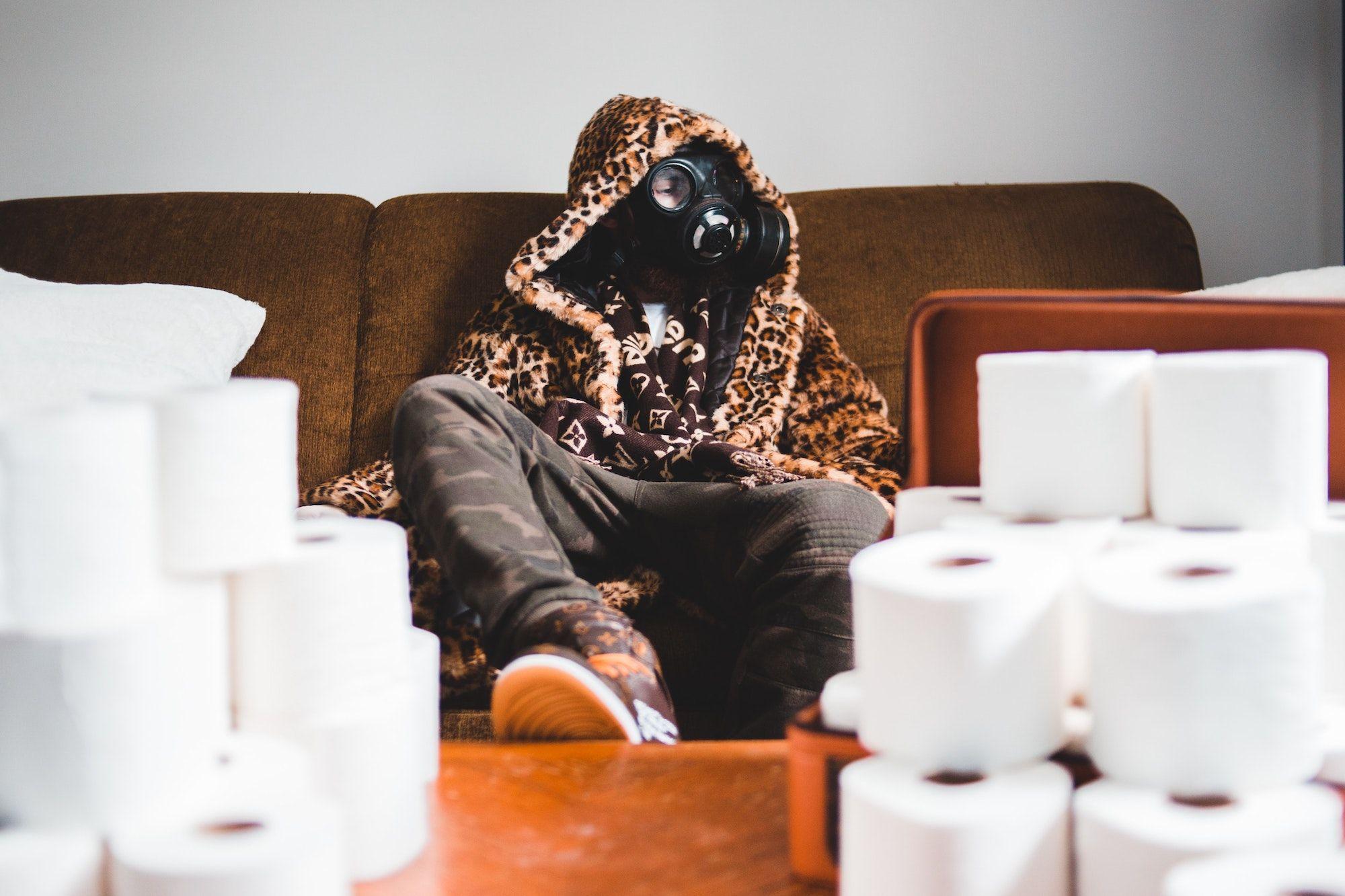 човек с противогаз, седнал на диван, вдигнал крак на маса отрупана с тоалетна хартия
